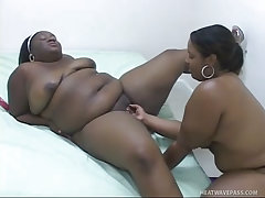 Two huge black fatties play with toys